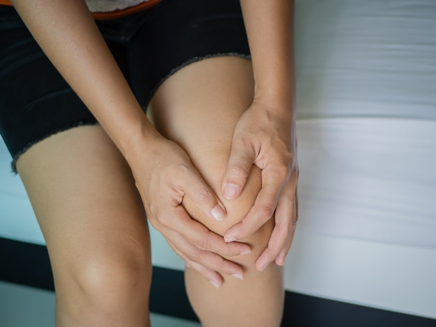 Closeup young woman massaging her painful knee, medical and health care concept.