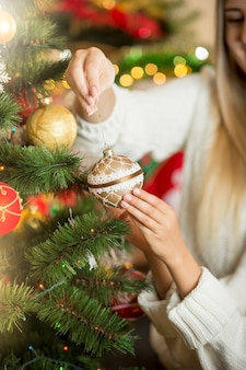 Closeup of young woman putting golden bauble on christmas tree