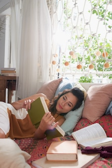 Closeup of young woman readin a book in the bed