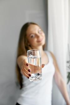 근접 촬영 젊은 여자 쇼 물 유리. 물의 투명 한 잔을 들고 행복 하 게 웃는 여성 모델의 초상화.