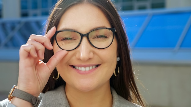 Closeup of a young woman straightening glasses and smiling at the camera