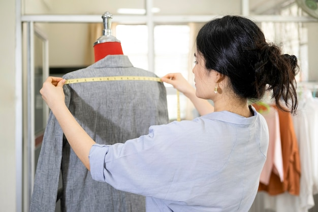 Closeup young woman tailor taking measurements of jacket on mannequin.