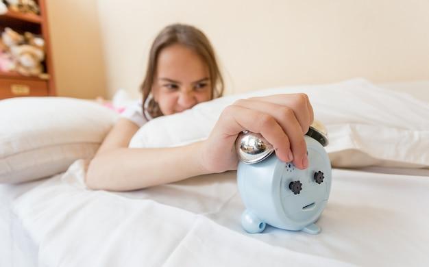 Closeup of young woman turning off alarm clock