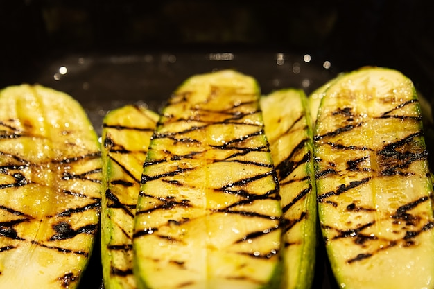 Closeup of zucchini grilled lying on a black frying pan