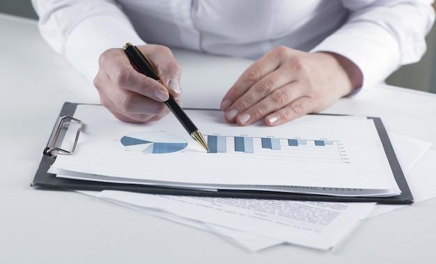 Closeupbusiness woman analyzing marketing graphics