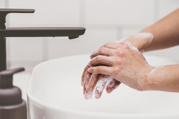 코비드19의 집에서 욕실에서 수도꼭지로 손을 씻는 클로즈업 아시아 여성
