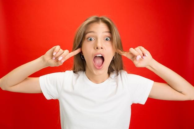 Закрывание ушей. портрет молодой кавказской женщины с яркими эмоциями на красной стене с copyspace. блондинка модель.
