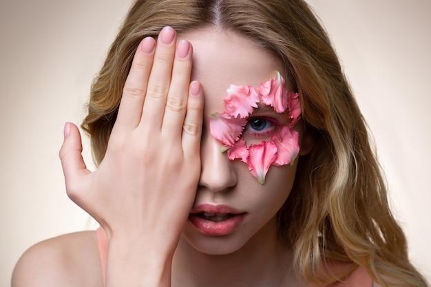 閉会の顔。別のピンクの花びらを持っている間彼女の顔の一部を閉じるブロンドのウェーブのかかった髪を持つ魅力的なモデル