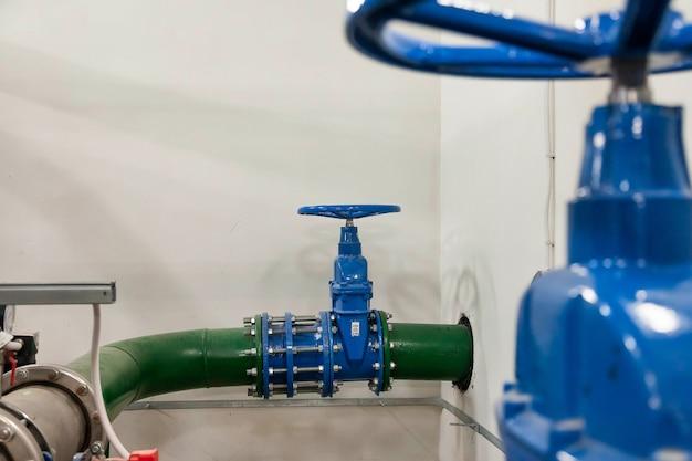 ウォーターポンプステーションの閉鎖バルブは、高圧水を供給するための工業室にある水タンクを備えたパイプラインです。散水管と圧力制御システム。サイトのコピースペース