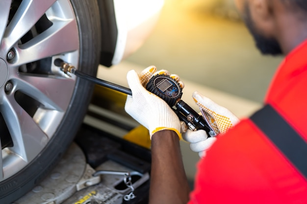 Closu up black mechanic inflating a tire in service station. checking air pressure with gauge