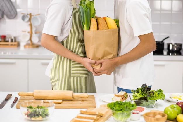 Молодая азиатская пара closuep из лгбт на кухне держит свежие сырые продукты перед приготовлением, чтобы отпраздновать день святого валентина