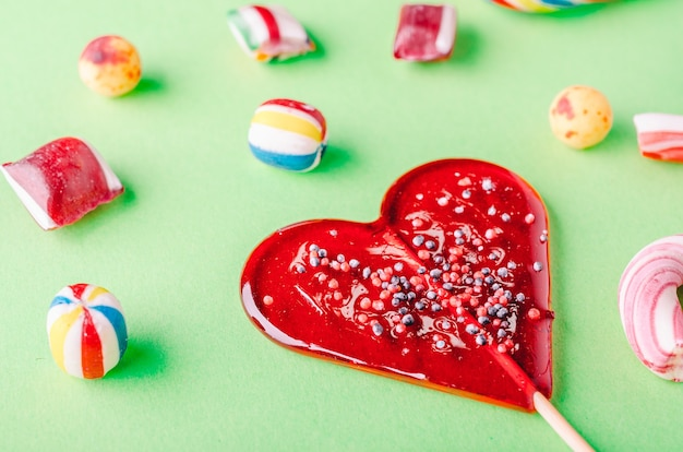 Inquadratura ravvicinata di un lecca-lecca a forma di cuore e altre caramelle su una superficie verde