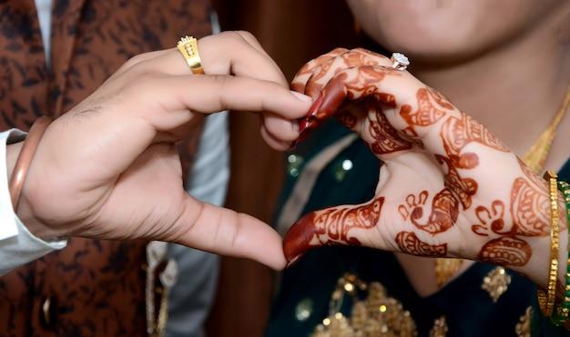그들의 손으로 심장 제스처를 만드는 젊은 신혼 부부의 근접 촬영