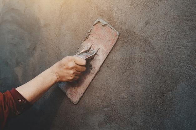 Рука closup рабочих штукатурка на стене на открытом воздухе на строительной площадке