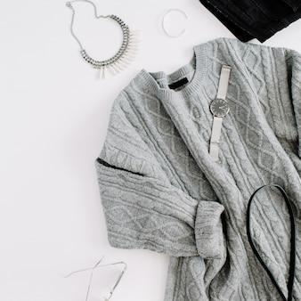 布とアクセサリー。暖かいセーター、ジーンズ、財布、時計、サングラスを使ったフラットレイの女性のカジュアルなスタイル。上面図。