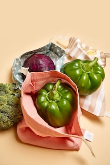 Cloth cotton shopping bags for groceries with vegetables. beige background. no plastic
