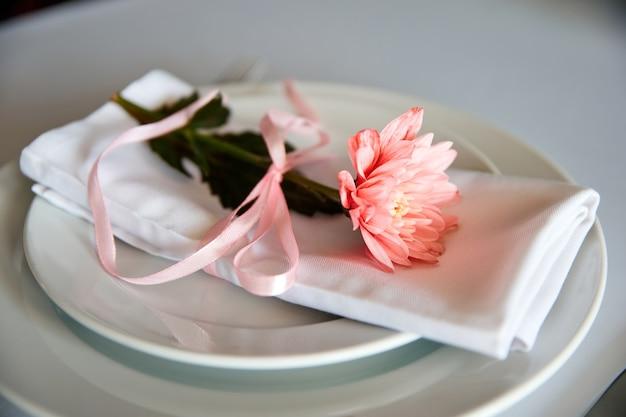 Салфетки из ткани с розовыми хризантемами лежат на тарелке в ресторане. крупный план, выборочный фокус