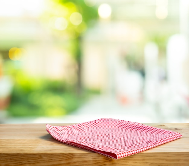 Cloth napkin on wood table with glass window background.for disign product display.