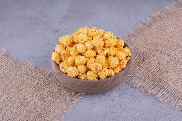Pezzi di stoffa sotto una ciotola di legno piena di popcorn aromatizzati su fondo marmo. foto di alta qualità