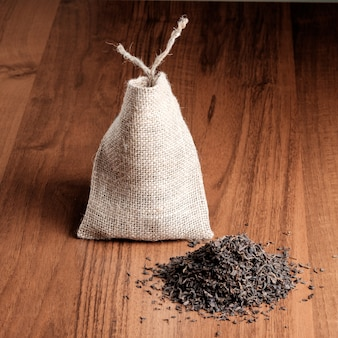 Cloth sack and dry tea on wooden floor