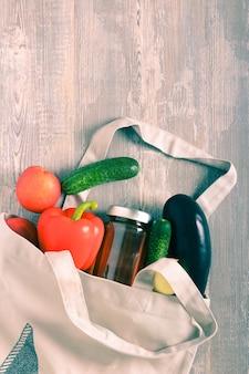 木製の背景の上に食べ物と布ショッパーバッグ。エコ再利用可能なバッグ環境にやさしいコンセプト