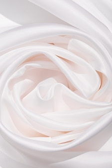 Ткань текстуры фона белого цвета. яркая атласная ткань со складками