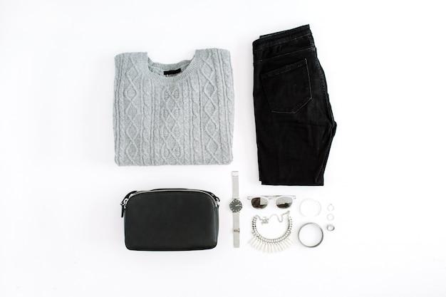 白い背景の上の服とアクセサリー。暖かいセーター、ジーンズ、財布、時計、サングラスを使ったフラットな女性スタイルの外観。上面図。