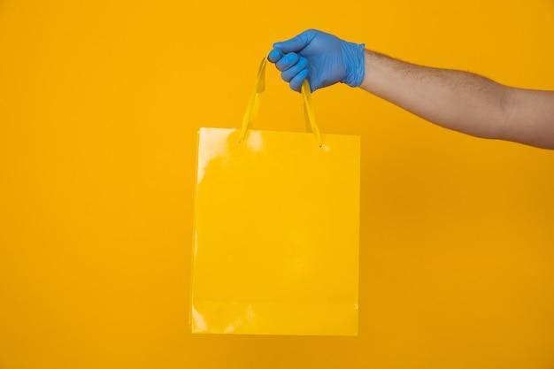 Доставка одежды и подарков в карантинное время. рука курьера в перчатке с хозяйственной сумкой.