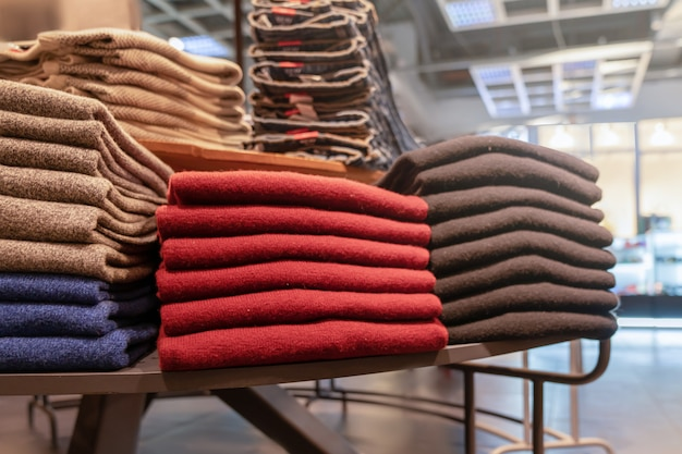 Clothes are neatly stacked on the shelves in the store. pullovers, sweaters warm of different colors are plain. red and other warm shades. close up
