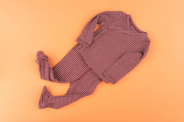 Clothes of baby girl on orange background top view