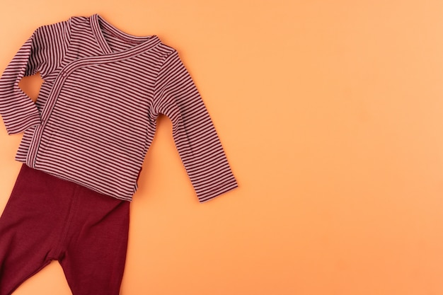 Clothes of baby girl on orange  top view