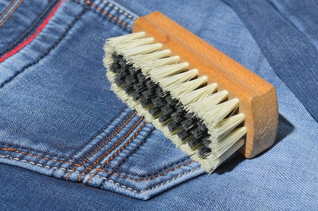 A clothes brush lies on folded jeans.