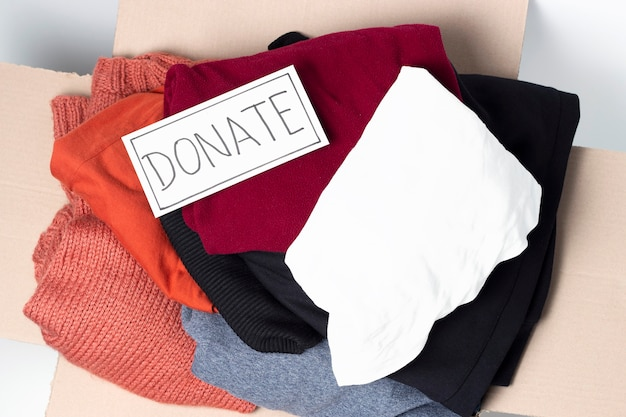 Clothes in a cardboard box and the inscription donate, top view