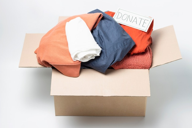 Clothes in a cardboard box and the inscription donate