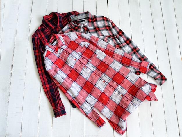 Концепция одежды. три клетчатые рубашки на деревянном фоне. вид сверху