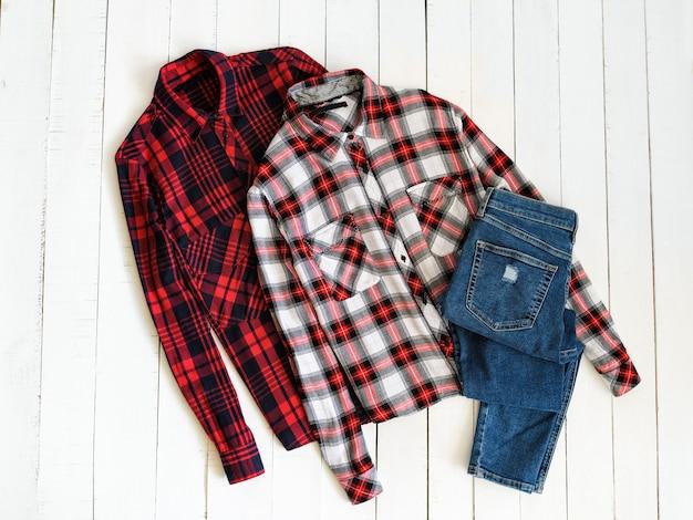 Концепция одежды. две клетчатые рубашки и джинсы на деревянном фоне. вид сверху