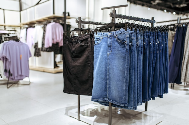 Clothes, denim skirts collection on racks in clothing store