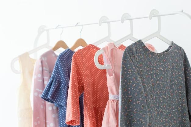 의류, 디자이너 및 중소기업 개념. 옷걸이에 많은 옷