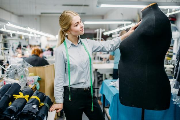 服のデザイナーがマネキンのドレスを測定します