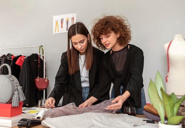 Designer di vestiti che lavorano in negozio