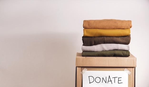 Пожертвование одежды, возобновляемая концепция. коробка использования старой ткани. подготовка одежды дома перед пожертвованием