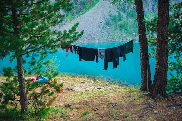 Одежды высушили на веревочке среди деревьев на солнечный день против ясной лазурной воды озера горы. активный отдых в горной местности. кемпинг в раю. удивительный пейзаж в горах. красивая природа.