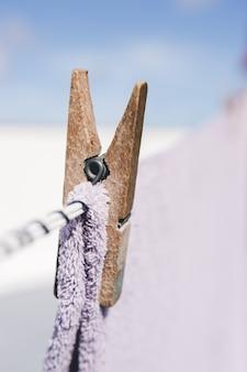 Сушка белья на открытом воздухе. крупным планом деревянная прищепка. одежда висит на веревке.