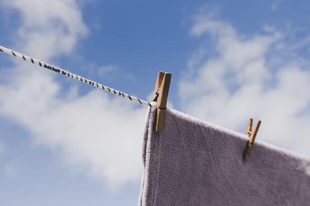 屋外で乾燥する服。クローズアップ木製洗濯はさみ。ロープをぶら下げ服。