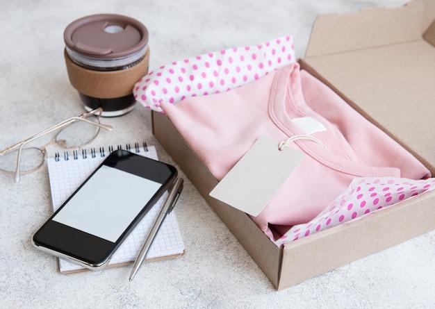Одежда для детей в открытой картонной коробке. концепция покупок в интернете. доставка одежды.