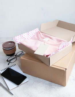 開いた段ボール箱の子供服。オンラインショッピングのコンセプト。服の配達。