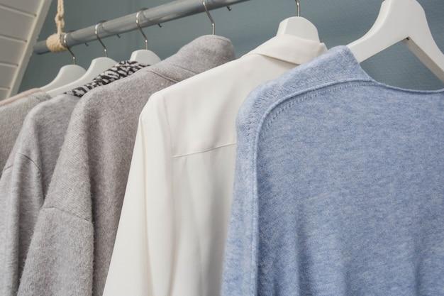 洋服は衣類ラックにぶら下がっています、白灰色と青、クローズアップ