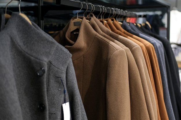 Clothes on a hanger autumn or winter coat at men's clothing store. season time of sales and discounts.