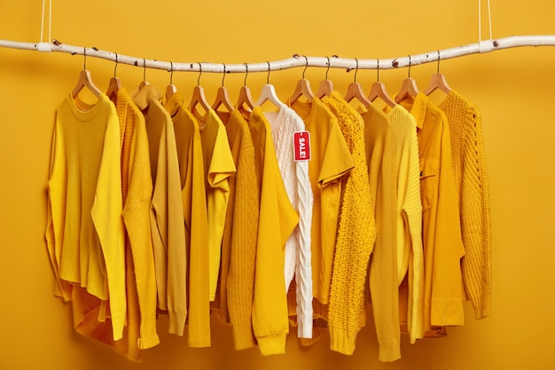 Clothes hanger filled with solid yellow female sweaters. one white sweater stands out of collection, being on sale.