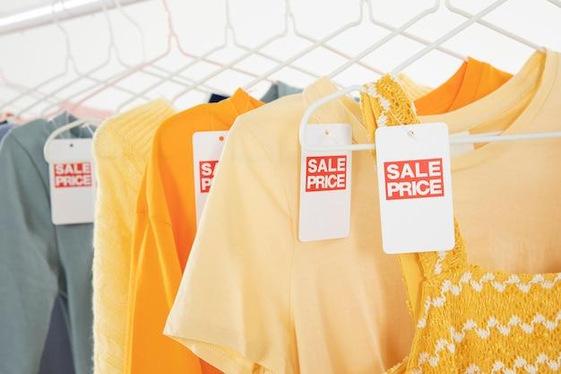 Одежда, висящая на вешалках в гардеробной